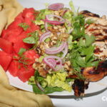 chicken and watermelon balsamic salad, topped with walnuts, red onions, parsley and dill