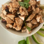 qdoba chicken in a bowl with cilantro and lime wedges